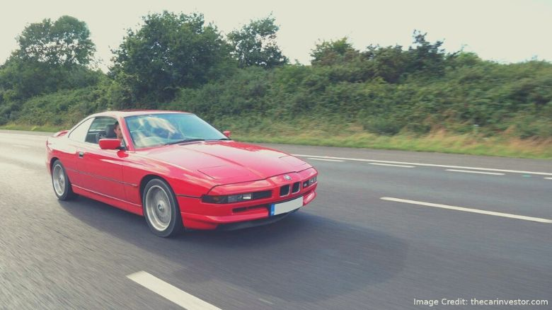 A red BMW 840 on the road