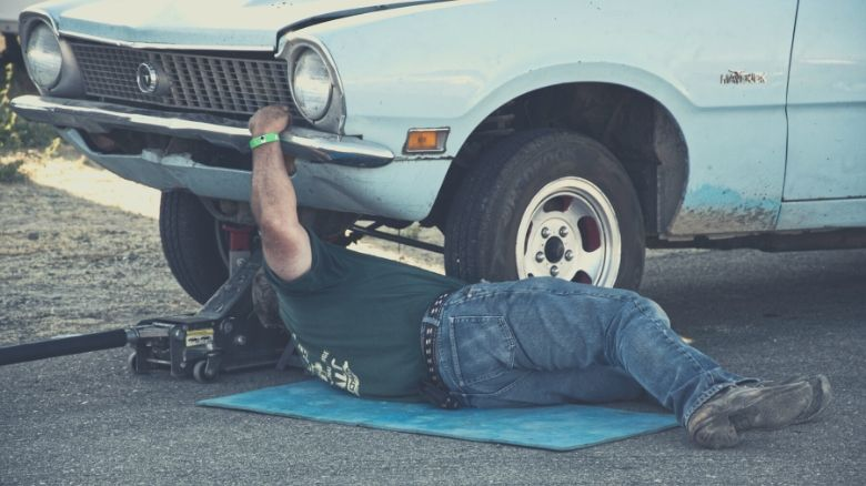A man working underneath his car using a jack