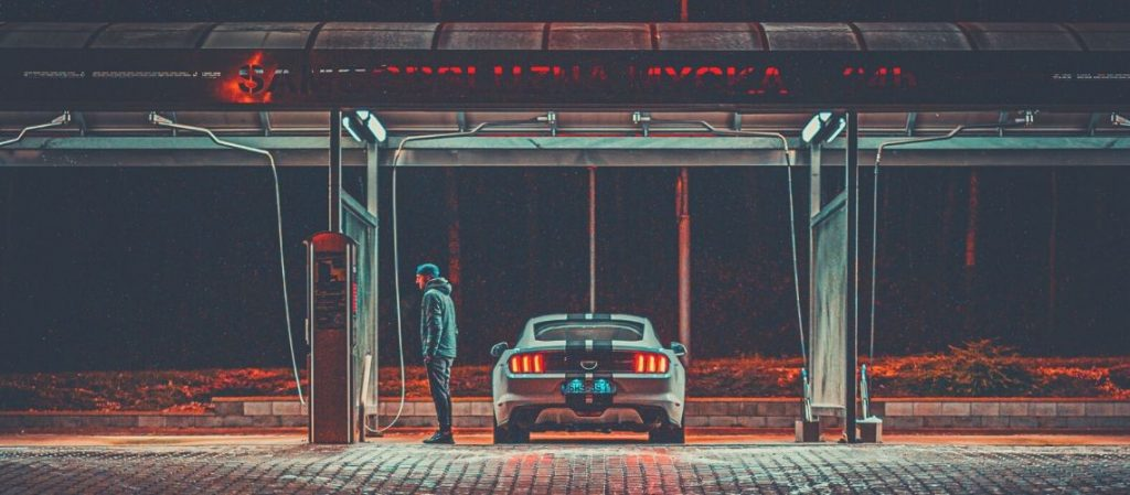 A man standing at a gas station with his Ford Mustang