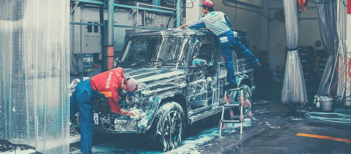 A black Mercedes being washed by two men